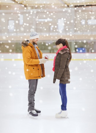 iceskates: people, love, proposal, sport and leisure concept - happy couple with engagement ring on skating rink Stock Photo