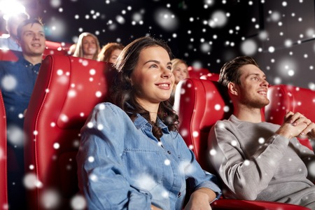 christmas movies: cinema, entertainment and people concept - happy friends watching movie in theater with snowflakes Stock Photo