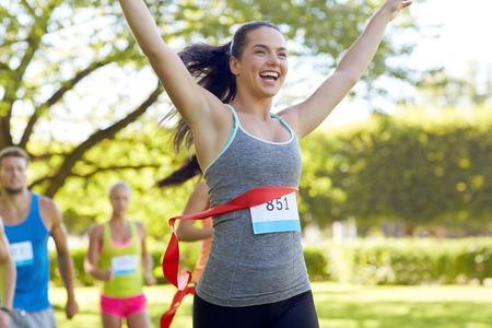 Úspěch: fitness, sport, vítězství, úspěch a zdravého životního stylu koncept - šťastná žena, vyhrát závod a přichází jako první do konce červenou stuhou přes skupinu sportovců běží maraton s čísly odznaků venku Reklamní fotografie