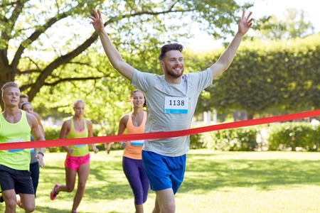 fitness, sport, victory, success and healthy lifestyle concept - happy man winning race and coming first to finish red ribbon over group of sportsmen running marathon with badge numbers outdoors Stock Photo