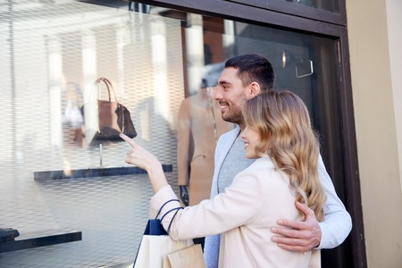sale, consumerism and people concept - happy couple with shopping bags pointing finger to shop window on city street