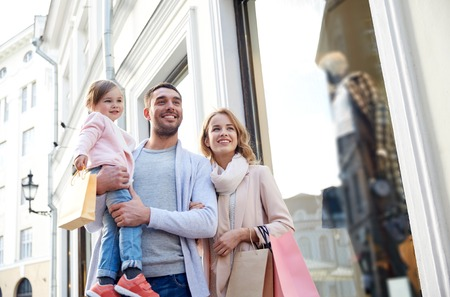 luxury lifestyle: sale, consumerism and people concept - happy family with little child and shopping bags in city Stock Photo