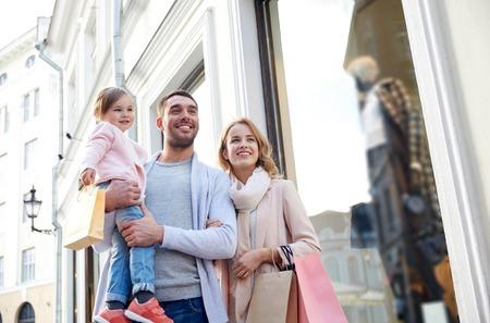 família: venda, o consumismo e as pessoas conceito - família feliz com criança pequena e sacos de compra na cidade