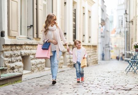 madre soltera: venta, el consumismo y el concepto de la gente - la madre y el niño feliz con bolsas de compras caminando por la calle de la ciudad