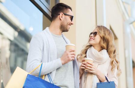 parejas jovenes: venta, el consumismo y el concepto de la gente - pareja feliz con bolsas de la compra y vasos de papel caf� en escaparate en la ciudad
