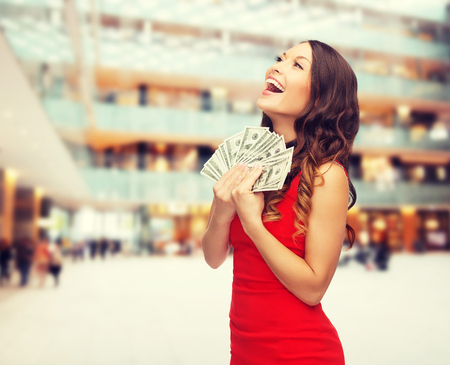 christmas profits: christmas, holidays, sale, banking and people concept - smiling woman in red dress with us dollar money over shopping center background