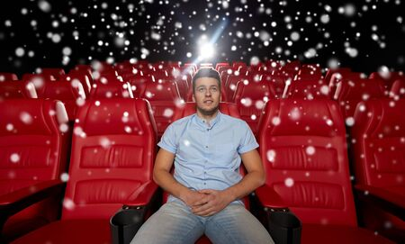 alone in the dark: cinema, entertainment and people concept - happy young man watching movie alone in empty theater auditorium over snowflakes