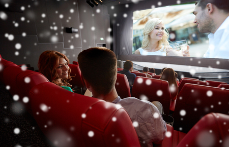 christmas movies: cinema, entertainment and people concept - happy friends or couple watching movie in theater on last row and talking from back over snowflakes