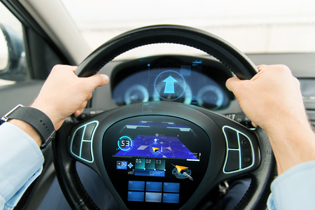 transport, technology, navigation, destination and people concept - close up of male hands holding car wheel and driving with gps navigator on wheel computer screen
