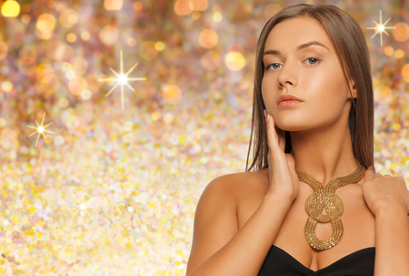 jewelry background: beauty, luxury, people, holidays and jewelry concept - beautiful woman wearing golden necklace over lights background Stock Photo