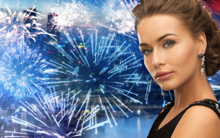 hollywood christmas: people, holidays and glamour concept - beautiful woman wearing earrings over firework at night city background