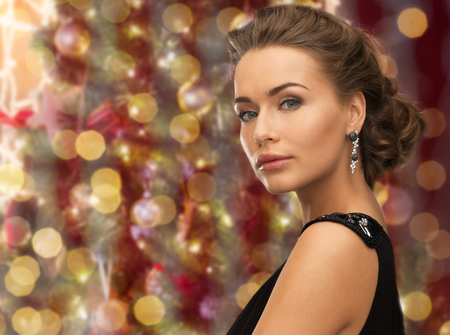 glamor: people, holidays, jewelry and glamour concept - beautiful woman wearing earrings over christmas lights background Stock Photo