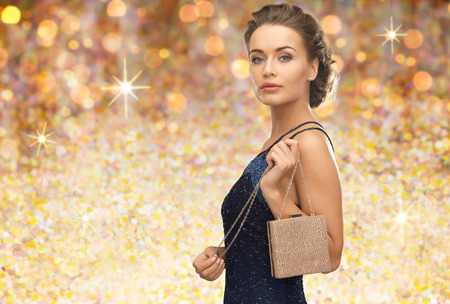glamour luxury: people, holidays, luxury and glamour concept - woman in evening dress with small handbag over golden lights background Stock Photo