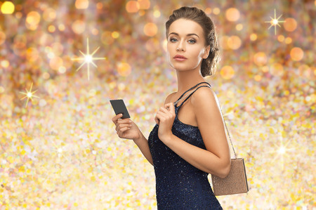 people, luxury, holidays and finance concept - beautiful woman in evening dress with vip card and handbag over golden lights background Imagens