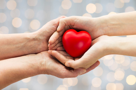 child hand: people, age, family, love and health care concept - close up of senior woman and young woman hands holding red heart over lights background Stock Photo