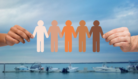 family unity: immigration, unity, population, race and humanity concept - multiracial couple hands holding chain of paper people pictogram over boats in sea background