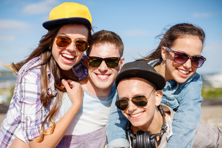 teen: summer holidays and teenage concept - group of smiling teenagers hanging outside