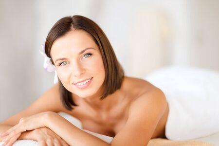 massieren: Gesundheit und Sch�nheit, Resort und Entspannungs-Konzept - sch�ne Frau mit Blume im Haar im Wellness-Salon auf dem Massage Schreibtisch liegen
