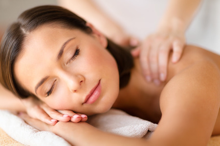 masaje: la salud, la belleza, la estaci�n y el concepto de relajaci�n - hermosa mujer con los ojos cerrados en sal�n del balneario que consigue masaje Foto de archivo