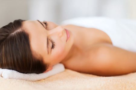 schoonheid: schoonheid en spa concept - mooie vrouw in de spa salon liggend op de massage bureau Stockfoto