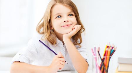 soñando: la educación y la escuela concepto - niña estudiante de dibujo con lápices en la escuela