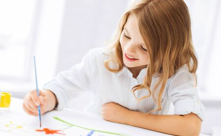 creation kit: education, school, art and painitng concept - little student girl painting picture Stock Photo