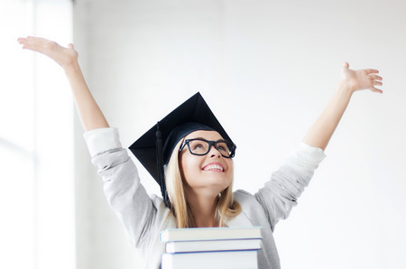 master degree: happy student in graduation cap with stack of books Stock Photo