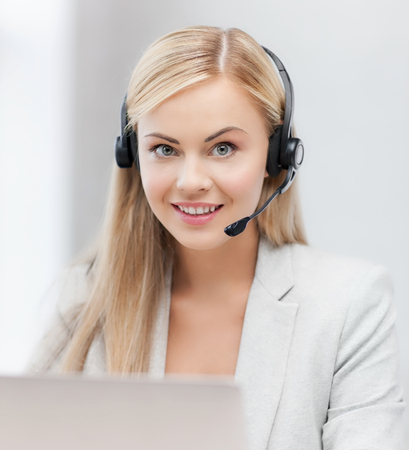 friendly: smiling female helpline operator with headphones and laptop