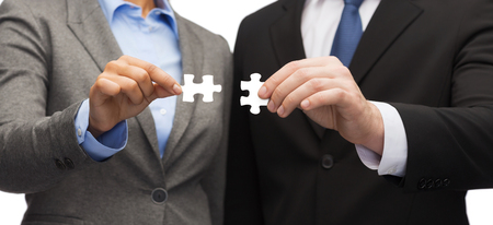linking: business concept - businessman and businesswoman trying to connect puzzle pieces in office Stock Photo