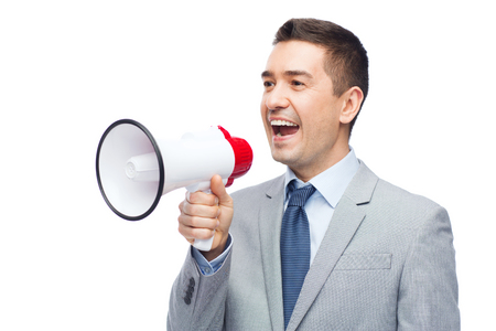 announcements: business, people and public announcement concept - happy businessman in suit speaking to megaphone