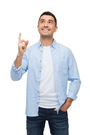standing up: happiness, gesture and people concept - smiling man pointing finger up Stock Photo