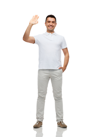 greeting, gesture and people concept - smiling man in blank white t-shirt waving hand