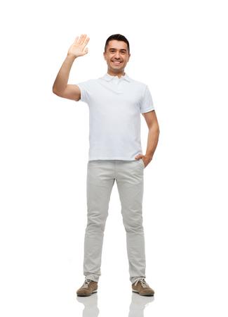 personas saludandose: hombre sonriente en blanco camiseta blanca mano que saluda - saludo, gesto y el concepto de la gente