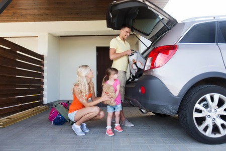 private insurance: transport, leisure, travel, road trip and people concept - happy family packing things into car at home parking