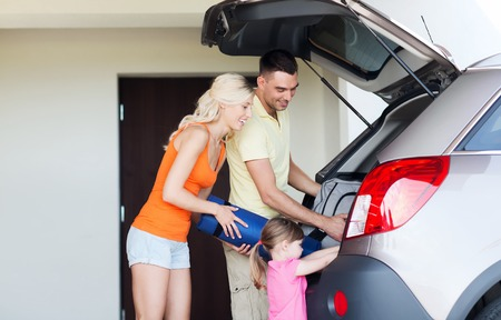 family together: transport, leisure, travel, road trip and people concept - happy family packing things into car at home parking