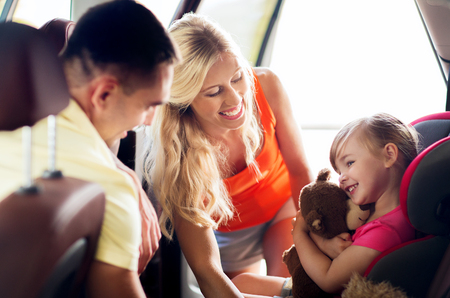 animal family: family, transport, safety, road trip and people concept - happy parents with to little girl in baby car seat hugging teddy bear toy Stock Photo