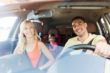 drive car: family, transport, safety, road trip and people concept - happy man and woman with little child driving in car