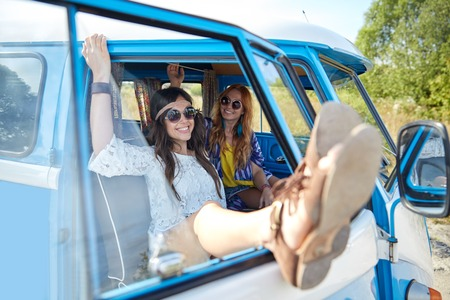 gipsy: summer holidays, road trip, vacation, travel and people concept - smiling young hippie women resting in minivan car