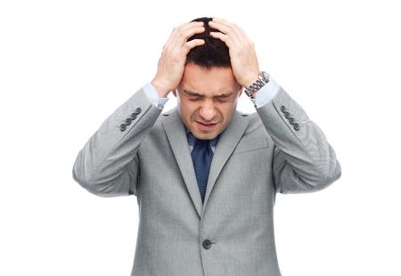 business concept: business, people, crisis and fail concept - businessman in suit having head ache