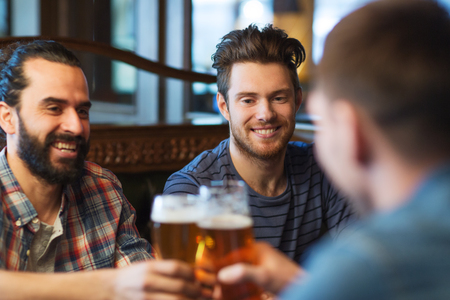 bar: people, men, leisure, friendship and celebration concept - happy male friends drinking beer and clinking glasses at bar or pub