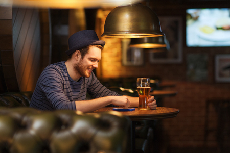 cell phone addiction: people and technology concept - happy man with smartphone drinking beer and reading message at bar or pub Stock Photo
