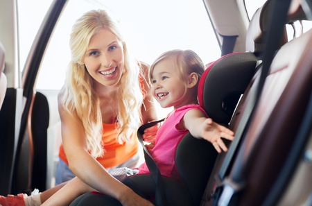 fastening: family, transport, safety, road trip and people concept - happy mother fastening child with car seat belt