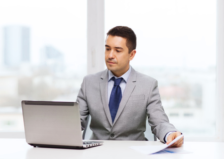 happy workers: business, people, paperwork and technology concept - businessman with laptop computer and papers working in office