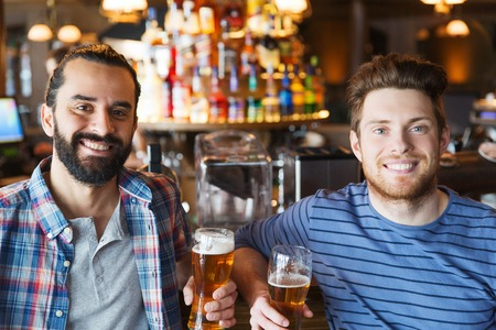 best party: people, leisure, friendship and bachelor party concept - happy male friends drinking beer and talking at bar or pub
