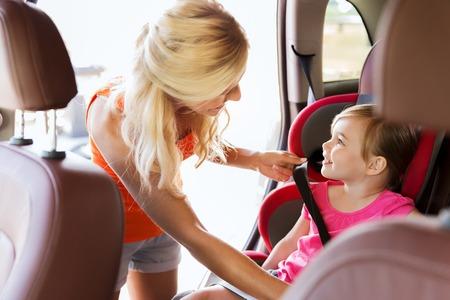 asiento coche: la familia, el transporte, la seguridad, viaje por carretera y la gente concepto - la madre feliz de fijación niño con el cinturón de seguridad del coche