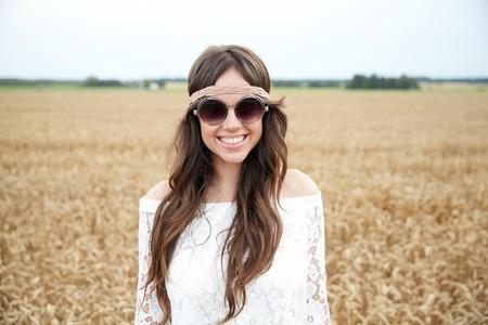 mujer hippie: naturaleza, verano, la cultura juvenil y la gente concepto - joven hippie sonriente en gafas de sol en el campo de cereales