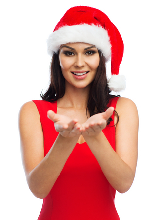 empty of people: people, holidays, christmas and advertisement concept - beautiful sexy woman in santa hat and red dress showing something on empty hands Stock Photo