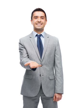 imaginary: business, people and office concept - happy smiling businessman in suit showing something imaginary on empty palm