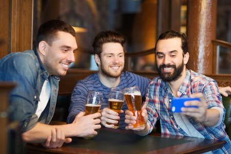 pub: people, men, leisure, friendship and technology concept - happy male friends drinking beer and taking selfie with smartphone at bar or pub