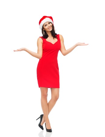 woman in red dress: people, holidays, christmas and advertisement concept - beautiful sexy woman in santa hat and red dress showing something on empty hands Stock Photo